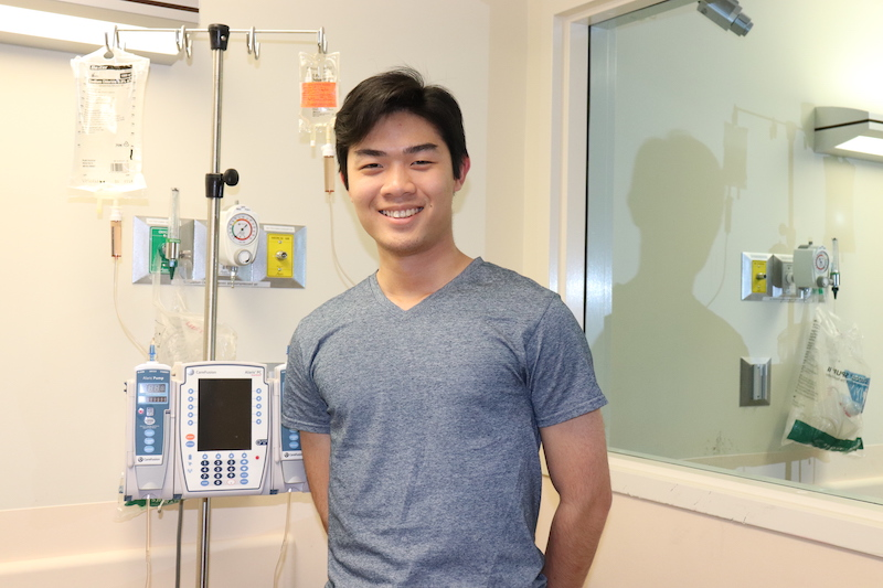 Key Nguyen smiles in front of the Department of Nursing at the University of Vermont.