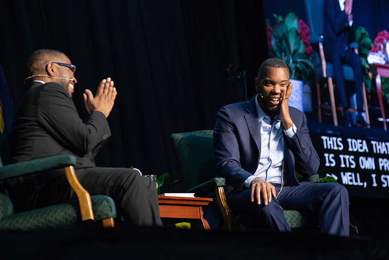 Poet Major Jackson and author Ta-Nehisi Coates seated on stage, both smiling.