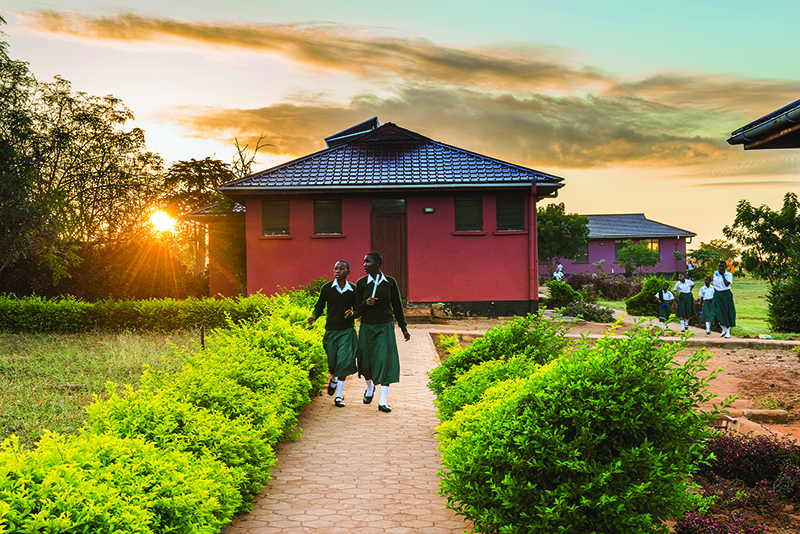 Young women in school uniform walking out front of a girl's school in Tanzania