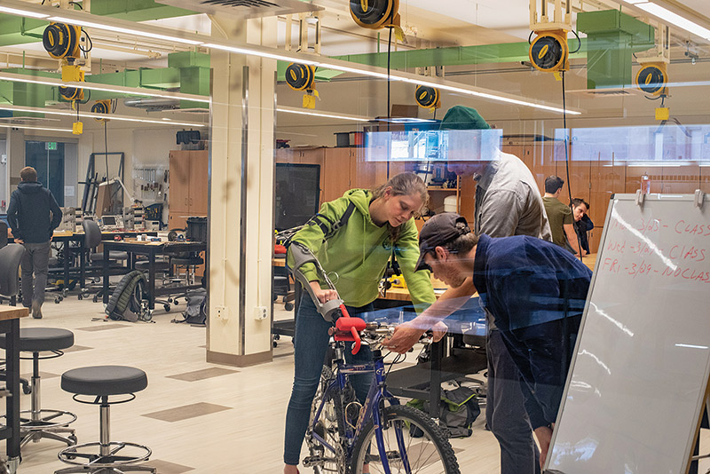 Students working on a mechanical arm operating a bike in the Votey Design Studio.