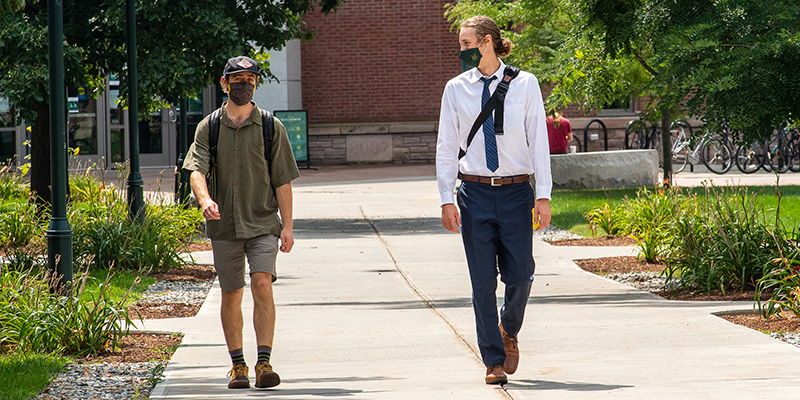 Two people walk in masks in front of UVM's Davis Center